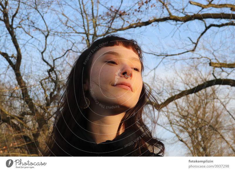 Porträt einer jungen lächelnden Frau unter kahlen Bäumen Frauengesicht Portrait portrait langhaarig Gesicht Identität weiblich blick schauen blicken