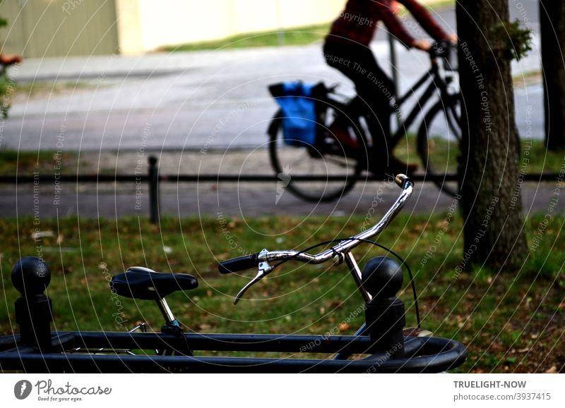 Auf dem Radweg neben der Straße fährt ein Mensch auf einem Damenfahrrad mit blauer Gepäcktasche vorbei, während im Vordergrund auf dem Grünstreifen ein Fahrrad mit Chrom farbigem Lenker an einen Zaun angelehnt steht; dazwischen ein Baum