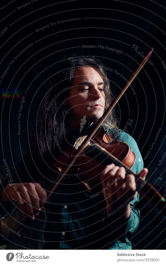 Mann spielt Geige in dunklem Raum spielen Musik Musiker Talent Fähigkeit Instrument Klang Melodie männlich dunkel Hobby Gesang professionell akustisch Spieler