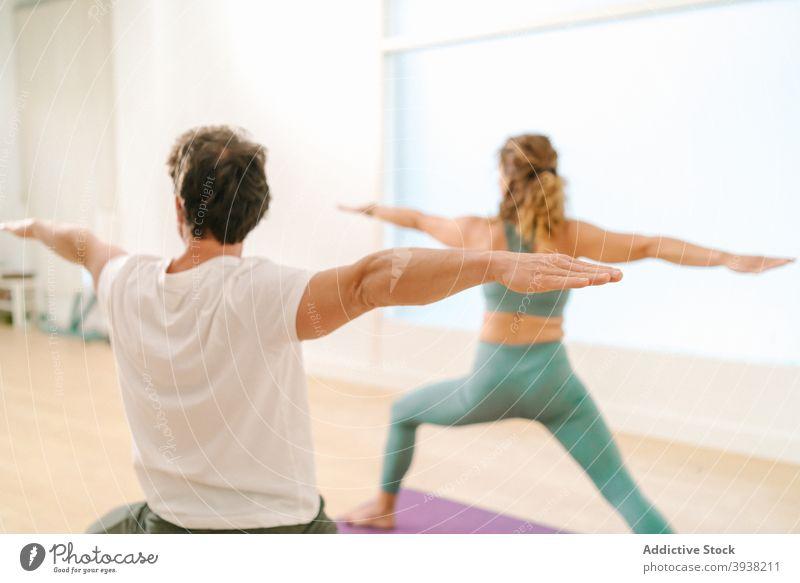 Mann und Frau tun Yoga in Warrior Pose im Studio Krieger-Pose üben Gleichgewicht Zusammensein Klasse Zen Barfuß ausdehnen Arme Atelier beweglich Asana Wellness