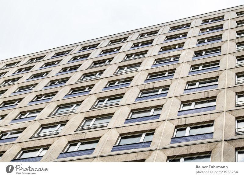 eine graue Fassade eines Hochhauses ragt in den Himmel Haus Wohnhaus anonym Fenster Architektur Gebäude Stadt Menschenleer Außenaufnahme Farbfoto Plattenbau