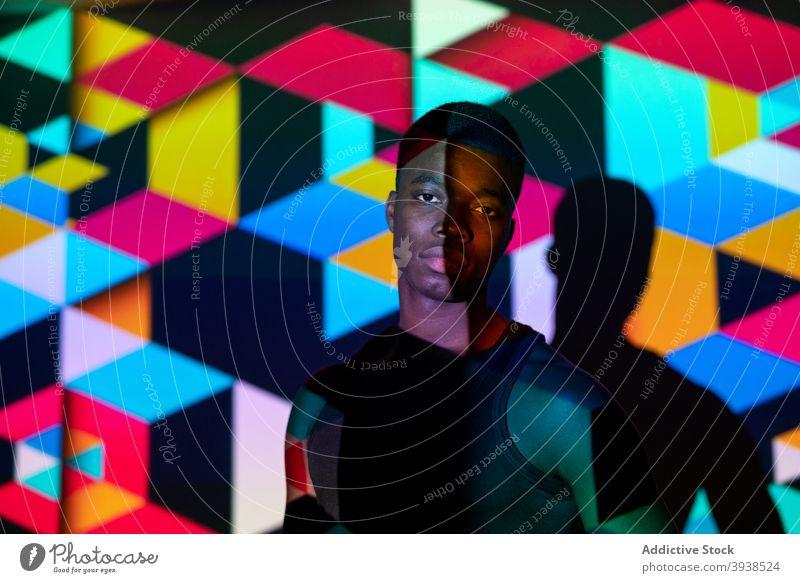 Ethnische Mann im dunklen Studio mit bunten Neon-Beleuchtung Atelier neonfarbig Licht Würfel Geometrie leuchten lebhaft farbenfroh Model männlich schwarz