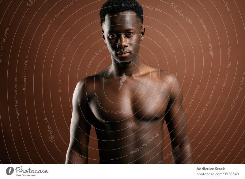 Stilvoller schwarzer Mann mit nacktem Oberkörper im Studio nackter Torso Jeanshose trendy Model muskulös ohne Hemd selbstbewusst männlich ethnisch
