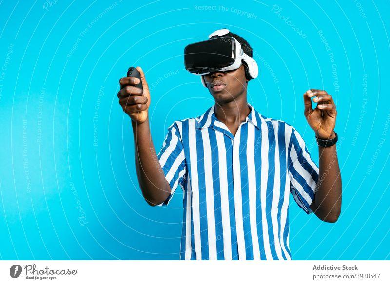Schwarzer Mann benutzt VR-Headset im Studio Schutzbrille Virtuelle Realität Videospiel spielen Erfahrung virtuell männlich schwarz ethnisch Afroamerikaner