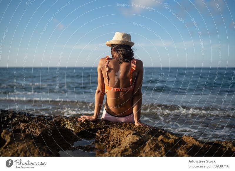 Unkenntlich weibliche Reisende genießen sonnigen Tag auf felsigen Meeresufer Frau Sonnenbad MEER Strand sich[Akk] entspannen Feiertag Resort reisen Küste jung