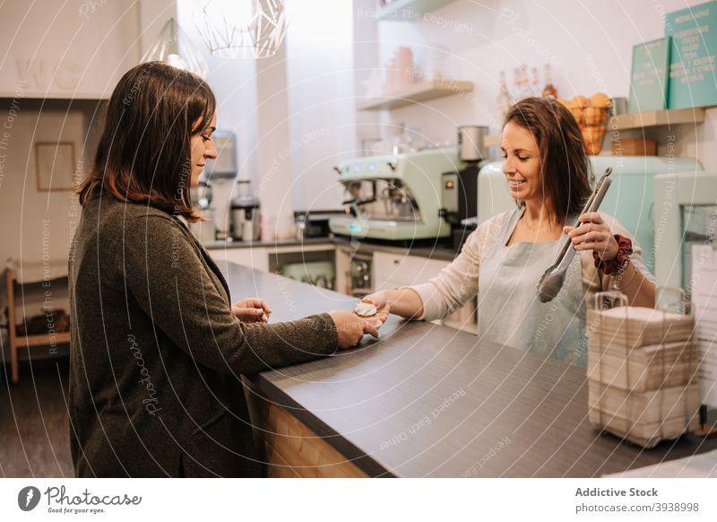 Frau kauft Süßigkeiten in der Konditorei Cupcake Kunde Verkäufer dienen süß Bonbon Dessert Glück Frauen Werkstatt heiter Einzelhandel kaufen Klient Käufer