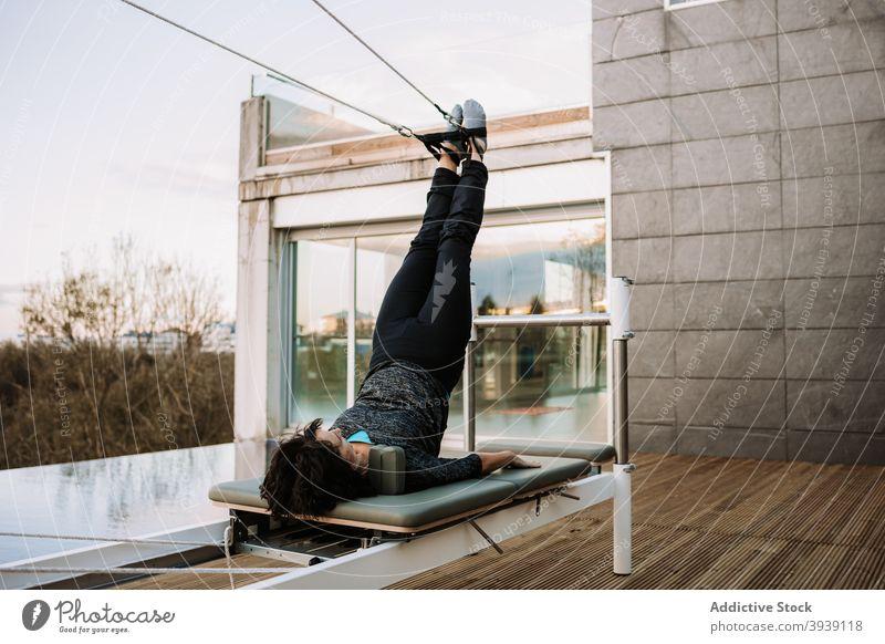 Ruhige Frau macht Yoga in Supported Shoulder Stand Pose auf Pilates-Maschine Asana Reformer Übung Gleichgewicht unterstützte Schulterstand-Pose Gurt Dehnung