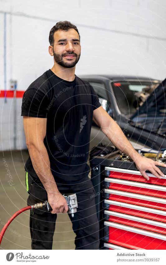Beschäftigter Mechaniker mit Werkzeugschrank in Autowerkstatt Kabinett Mann Techniker PKW Dienst Instrument Arbeit Station männlich Job Garage Flugzeugwartung