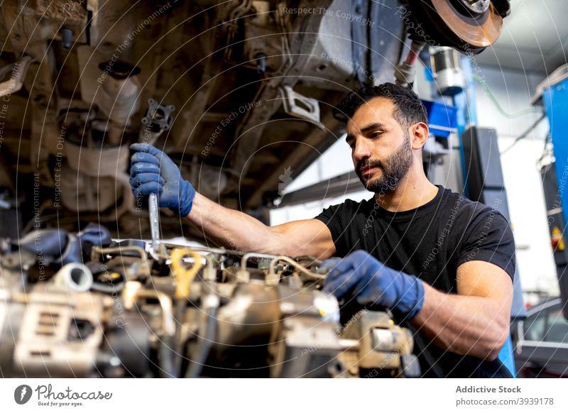 Männlicher Mechaniker repariert Auto in der Werkstatt Mann fixieren PKW Motor Dienst untersuchen Schraubenschlüssel männlich Techniker professionell Automobil