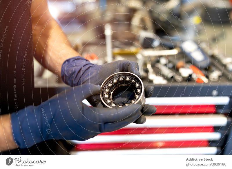 Crop männlich Mechaniker mit Auto Lager in der Werkstatt Mann PKW Dienst Detailaufnahme rund Arbeit Metall Rad Techniker Job Fahrzeug Flugzeugwartung modern