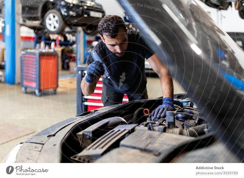 Techniker überprüft Auto im modernen Service untersuchen PKW Mechaniker Mann Dienst Taschenlampe Fackel Automobil Fahrzeug Reparatur Beruf männlich Verkehr