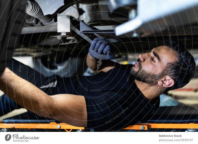 Männlicher Mechaniker schraubt Raddetail mit Schraubenschlüssel Mann PKW Dienst Automobil Reparatur schrauben Verkehr männlich Kletterpflanzen Techniker Lügen