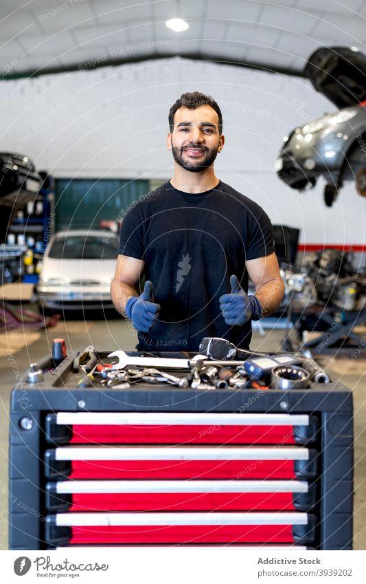 Lächelnder Mann mit Werkzeugschrank im Autoservice Kabinett PKW Mechaniker Techniker Dienst Instrument Daumen hoch gestikulieren männlich verschiedene Glück Job