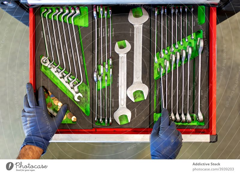 Crop-Mechaniker mit verschiedenen Werkzeugen in der Autowerkstatt Kabinett Schraubenschlüssel Mann Taste Sammlung PKW Dienst männlich Techniker Instrument