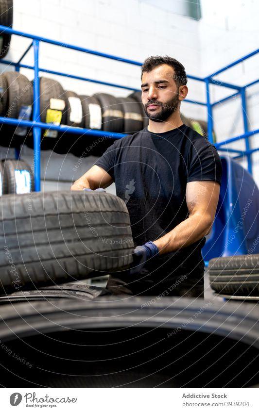 Mann mit Autoreifen in der Werkstatt PKW Mechaniker Reifen Dienst Techniker beschäftigt Arbeit männlich verschiedene Beruf ernst Handwerker Flugzeugwartung