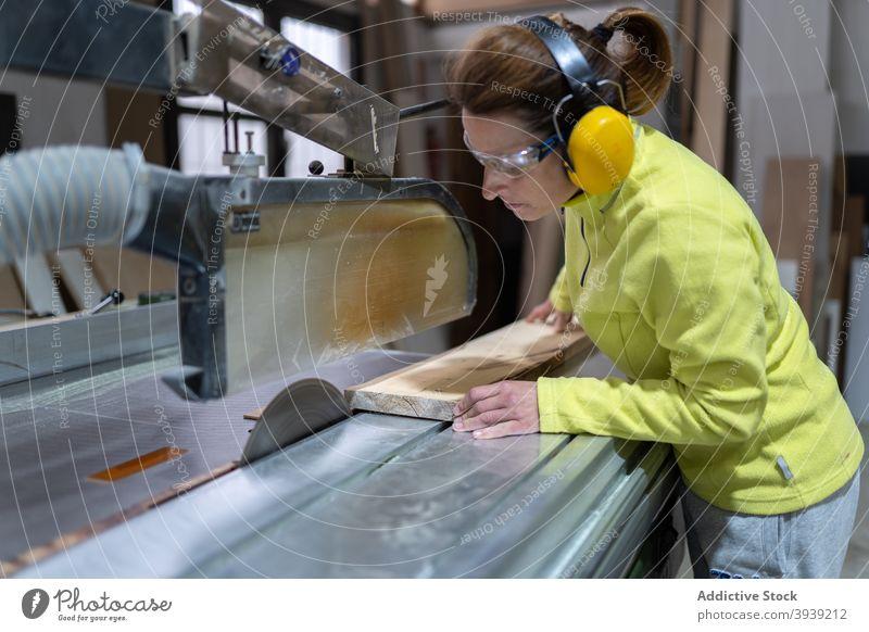 Seriöse Handwerkerin bei der Arbeit an der Tischsäge Frau Säge Holz Maschine Kunstgewerbler Hobelbank Fokus Tischlerarbeit Werkstatt Beruf hölzern Holzplatte