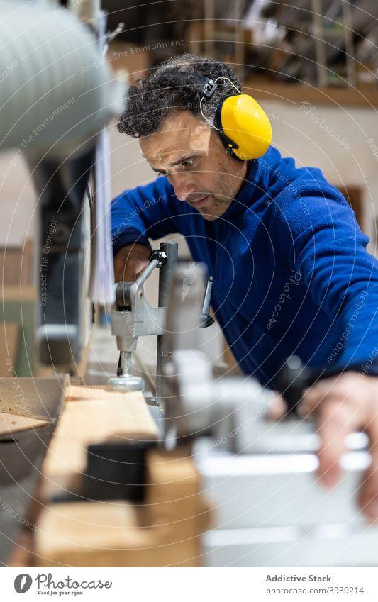 Professioneller Tischler beim Sägen eines Holzbretts in der Werkstatt Mann Maschine Job Zimmerer Tischlerarbeit Holzarbeiten Hobelbank Konzentration Beruf