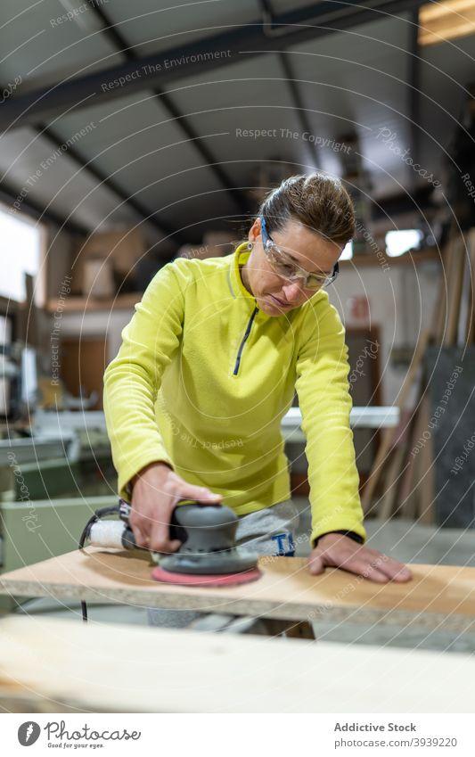 Konzentrierte Frau glättet Holz mit Schleifmaschine polnisch hölzern Schiffsplanken Maschine Tischlerarbeit professionell Meister Zimmerer Fähigkeit Orbital