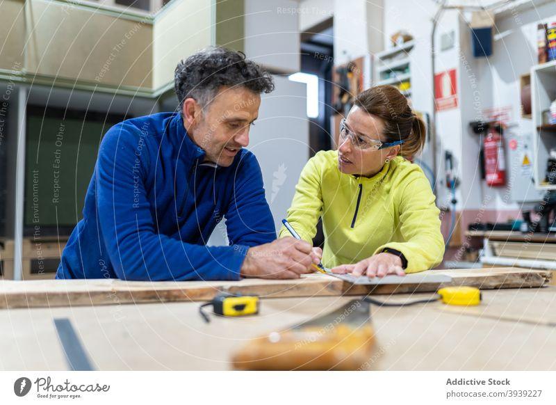 Fokussierte Kollegen messen Holz in moderner Werkstatt Holzarbeiten Zusammensein Konzentration Meister Tischlerarbeit Beruf professionell Mitarbeiterin Mann