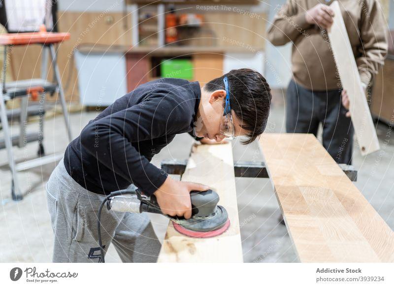 Konzentriertes Kind beim Polieren von Holz in der Werkstatt mit unkenntlichem Großvater Junge polnisch Schleifmaschine Maschine Hilfsbereitschaft Enkel Orbital