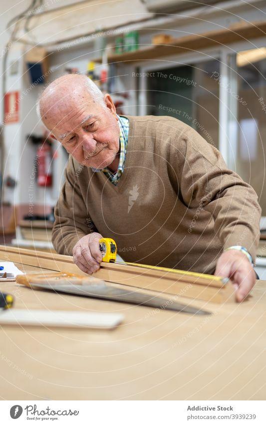 Senior-Handwerker bereitet Holz zum Sägen vor Mann messen Klebeband Tischlerin Werkstatt Maschine Arbeit Hobelbank Tischlerarbeit Kunsthandwerker Beruf männlich