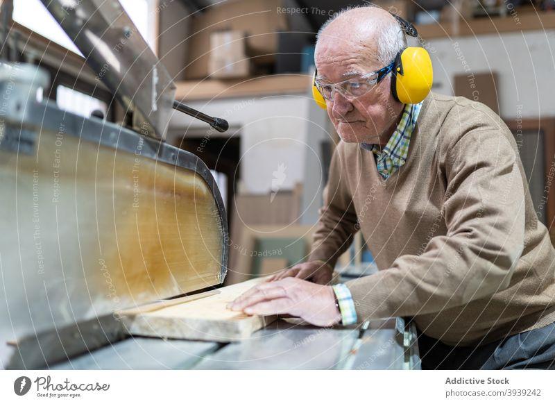 Seriöser Handwerker bei der Arbeit an der Sägetischmaschine Holz Maschine Kunstgewerbler Hobelbank Fokus Tischlerarbeit Werkstatt Beruf hölzern Holzplatte