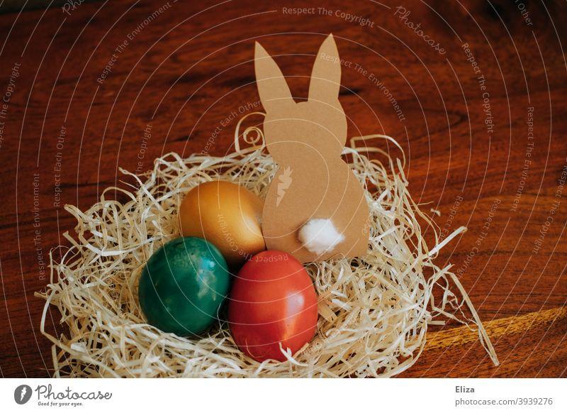 Osternest mit bunt gefärbten Eiern und einem gebastelten Osterhasen aus Papier Nest Ostereier Dekoration & Verzierung Osterdekoration Feste & Feiern