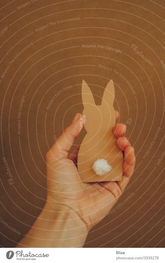 Hand hält einen Osterhase aus Papier Hase Ostern gebastelt Osterdekoration Osterbastelei Blume Schwanz Puschelschwanz braun