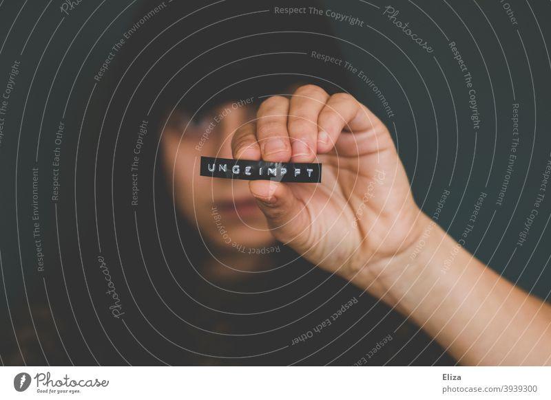 Eine frau hält ein Etikett auf dem das Wort ungeimpft steht in die Kamera Impfgegner Mittelfinger Impfung anti unsolidarisch Corona Covidiot impfen Solidarität