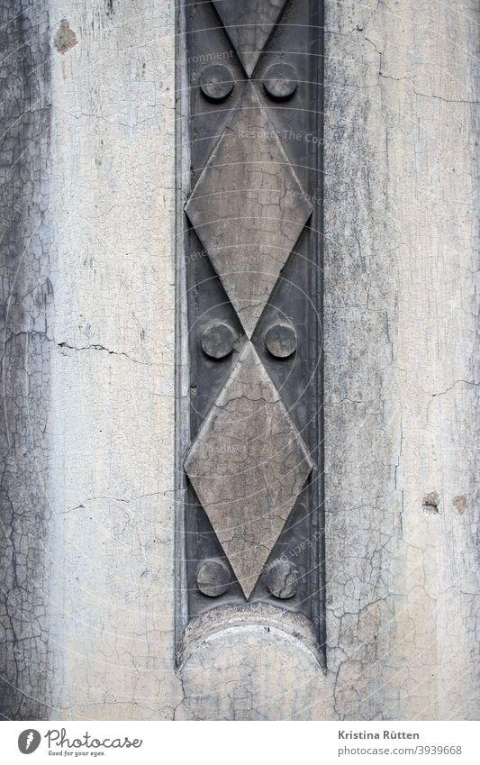 geometrisches muster an hausfassade ornament hauswand mauer gebäude dekorativ fassadenelement schmuckelement fassadengestaltung abstrakt punkte kreise rauten