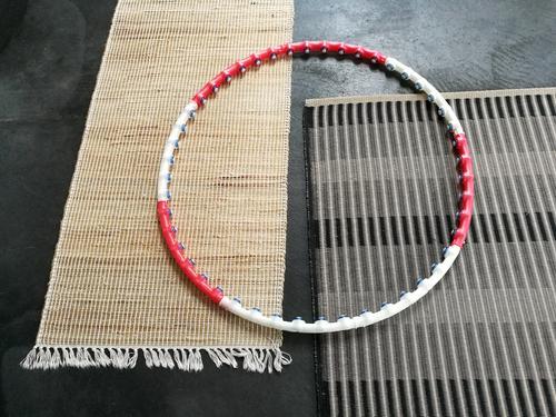 Hula Hoop Reifen in Rot und Weiß auf zwei schlichten modernen Teppichen aus Naturfaser auf dem grauem Betonboden einer Designerwohnung Fitness Sport Gymnastik