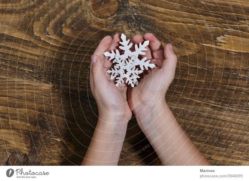 Kind hält eine hölzerne Schneeflocke. jung lustig Fröhlichkeit Schneefall Winter Lifestyle Studioaufnahme Hintergrund Halt Weihnachten Dekoration & Verzierung