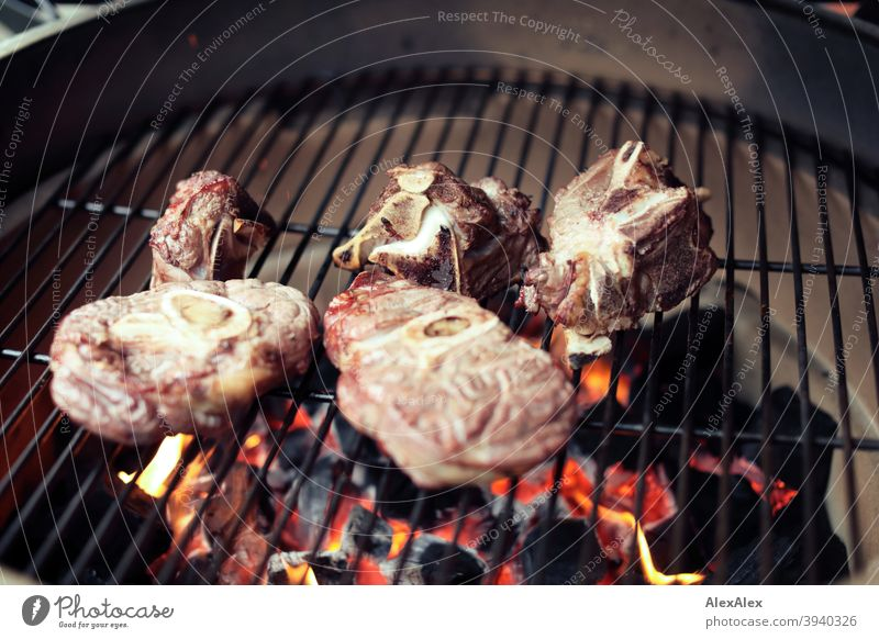 Mehrere Beinscheiben und Rinderknochen fertig gegrillt auf einem Kamado- Grill auf dem Grillrost Keramischer Grill Kamado Grill grün heiß Ruß Rust Töpferwaren
