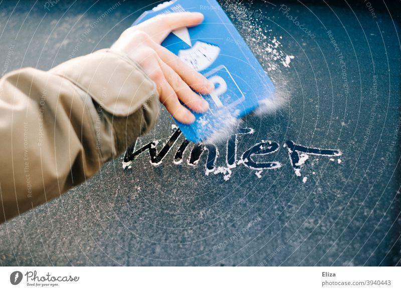 Hand kratzt mit einem Eiskratzer die vereiste Autoscheibe frei auf der das Wort Winter steht Frost kratzen Scheibe gefroren PKW Autofenster Windschutzscheibe