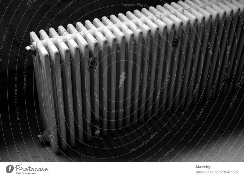Ausrangierter alter Heizkörper im dunklen Keller eines alten Landhaus in Bayern, fotografiert in klassischem Schwarzweiß Heizung Wärme Alt heizen Energie