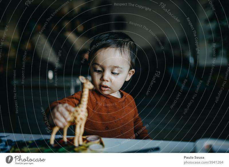 Kleinkind spielt mit Spielzeug Giraffe Spielen mehrfarbig Mensch niedlich Glück klein Kindergarten Baby Freude Kindheit authentisch Aktion Vorschule reizvoll
