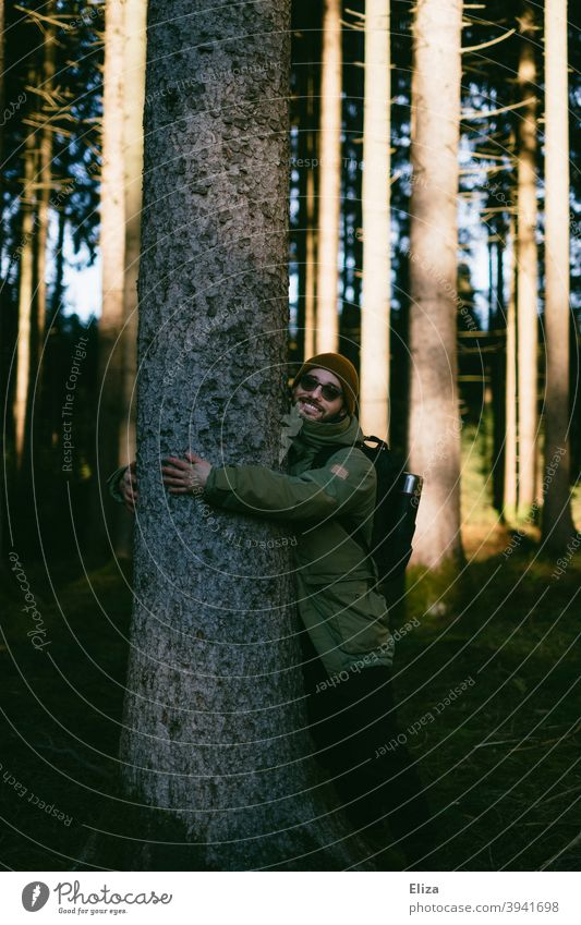 Ein Mann umarmt einen Baum im Wald ummarmen Umweltschutz Natur naturliebhaber naturverbunden Freude schützen Naturschutz Naturliebe Sonnenschein Winter Herbst