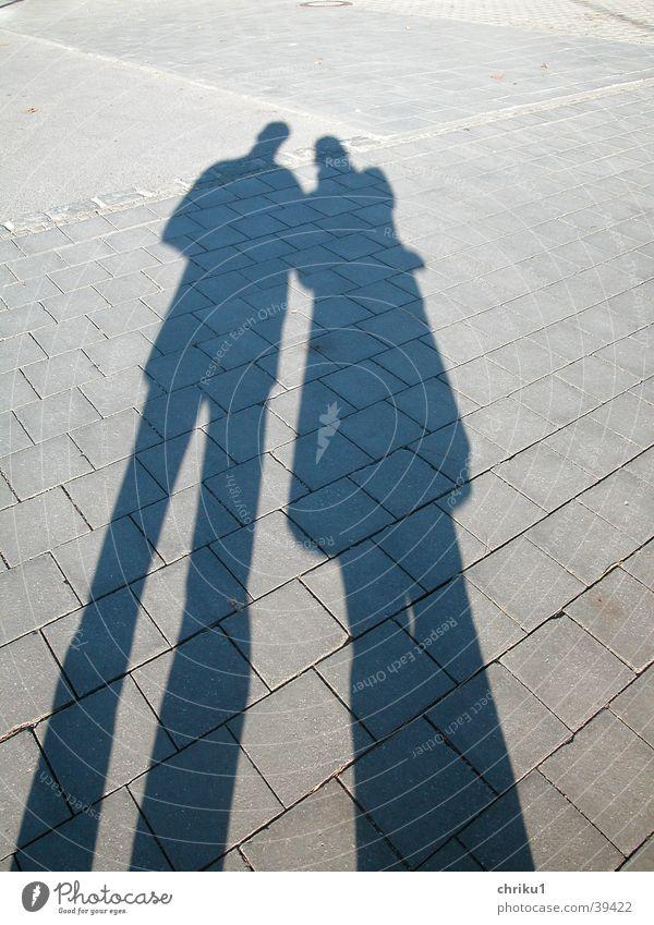 Schattenpaar Fußgängerzone Steinplatten Silhouette Mann Frau Kopfsteinpflaster Paar Graffiti Sonne Beine Liebe paarweise