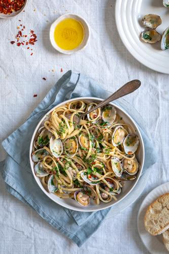 Draufsicht auf Pasta vongole, Linguini mit Venusmuscheln, roten Pfefferflocken und Olivenöl auf weißem Hintergrund mit blauer Serviette Food-Styling