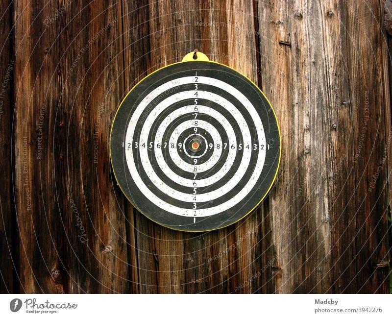 Runde Zielscheibe für Dartpfeile auf dem braunen Holz einer alten Scheune auf einem Bauernhof in Oberbayern Zielscheide Kreis Sport Freizeit Unterhaltung