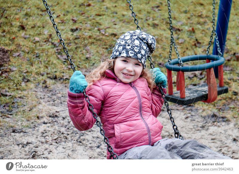 Mädchen auf der Schaukel Winter Spielplatz schaukeln Spielen Kind Kindheit fröhliches Kind Freude rote jacke lachen lachendes kind 3-8 Jahre Kindergartenkind