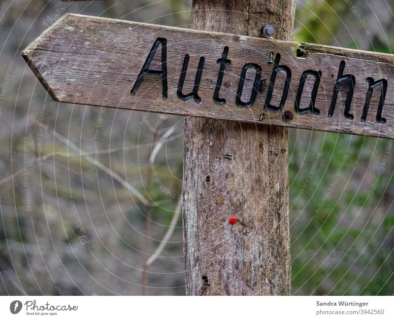 Autobahnschild aus Holz im Wald Richtung fahren Schilder & Markierungen Holzschild Verkehr Geschwindigkeit Verkehrswege Autofahren Außenaufnahme Farbfoto PKW