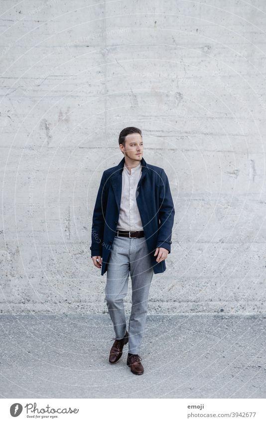 junger Mann, Business, draussen vor Betonwand männlich Erwachsener Junger Mann Geschäftsmann neugierig Blick zur Seite Zweifel kritisch Ganzkörperaufnahme gehen