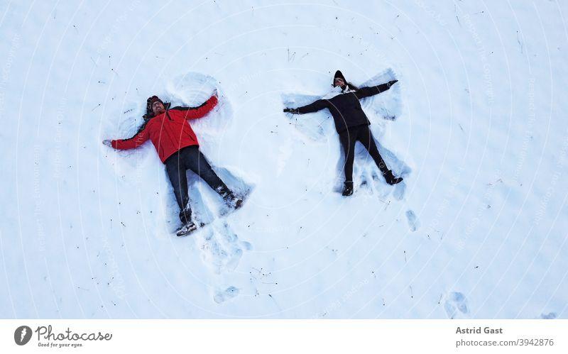 Drohnenaufnahme von einer Frau und einem Mann, die im Winter auf dem Boden liegend einen Schnee-Engel machen luftaufnahme drohnenfoto frau mann winter schnee