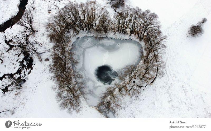 Luftaufnahme von einer Drohne von einem zugefrorenen See in Herzform oder Dreiecksform im Winter luftaufnahme drohnenfoto see gewässer eis winter schnee