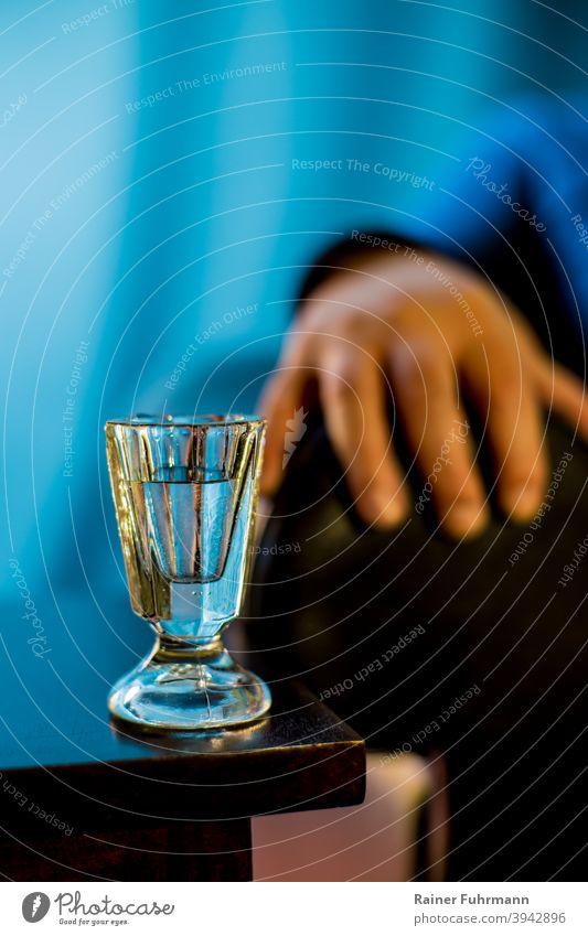 Auf einem Tisch steht ein altes Schnapsglas. Vor blauem Hintergrund sind Hand und Arm einer Person zu sehen. Alkohol Wodka Alkoholismus Alkoholiker Glas trinken