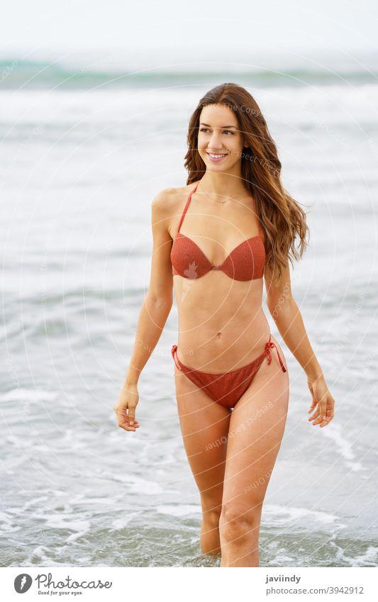 Frau mit schönen Körper genießt ihr Bad am Strand Bikini Wasser Sommer Freizeit Lifestyle Mädchen Küste Behaarung eine niedlich Frisur Saison MEER Sand Model