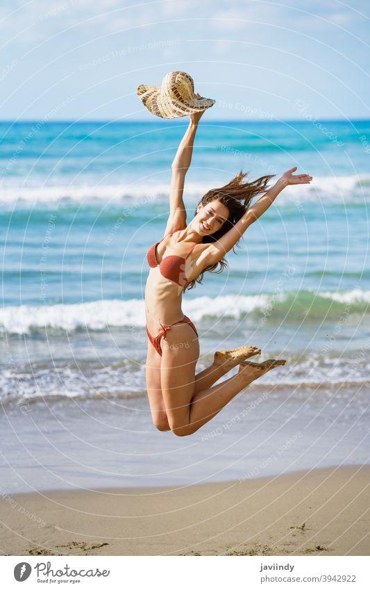 Junge Frau mit schönem Körper in Bademode springt auf einem tropischen Strand. springen springend Bikini Badeanzug Sommer Freizeit Lifestyle Mädchen Küste