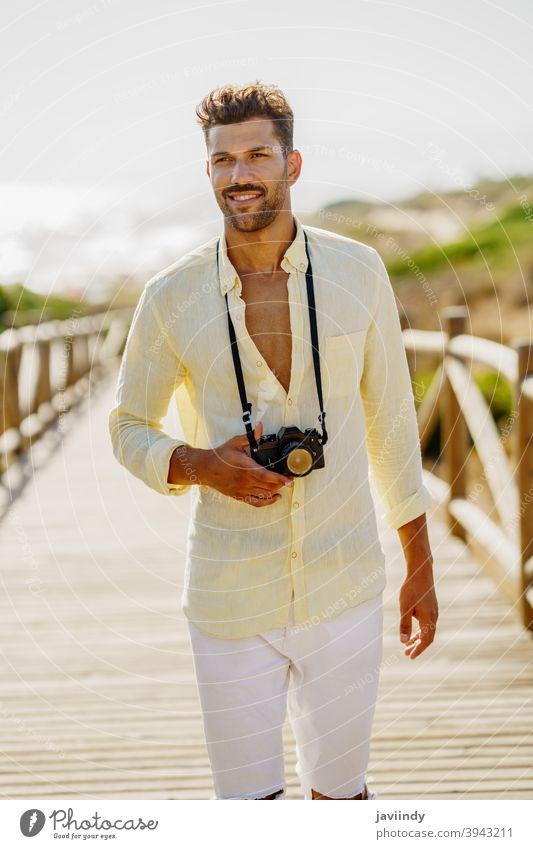 Lächelnder Mann beim Fotografieren in einer Küstengegend. Fotokamera Reisender Tourist Strand Sommer Natur Tourismus reisen Urlaub zahnfarben Feiertag Hobby