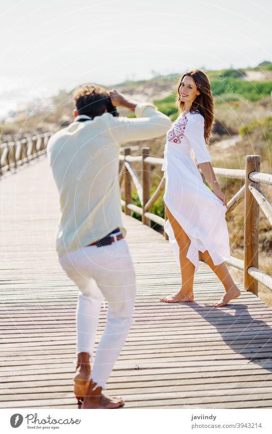 Mann, der seine Freundin bei einem Liebesausflug fotografiert. Paar Urlaub Fotograf Fotografieren Frau Reisender Tourist Resort Menschen Natur Freizeit Sommer